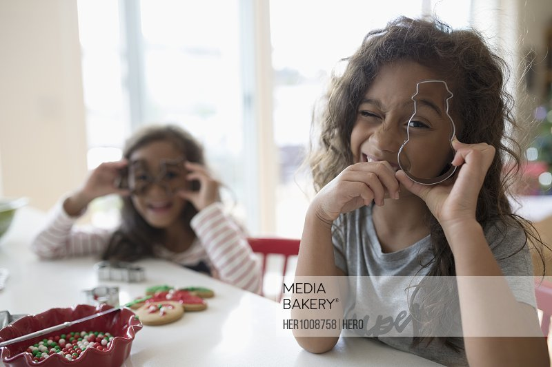 Portrait playful girl sisters with Christmas cookie cutters baking in kitchen