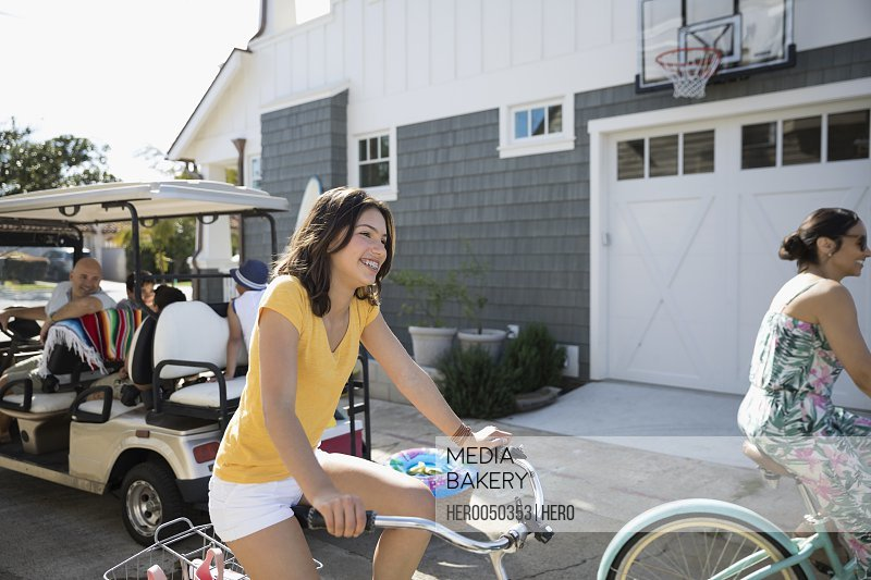 Smiling girl riding beach cruiser bicycle in summer beach house driveway