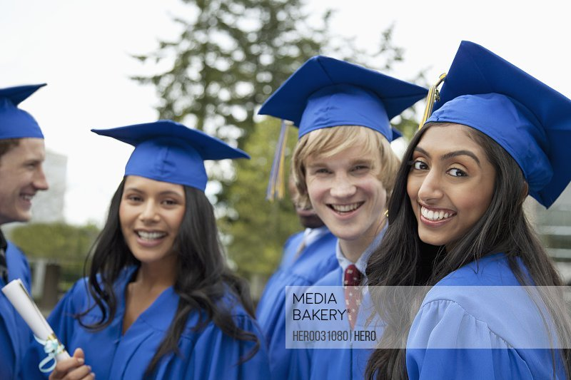 graduates posing and socializing outside