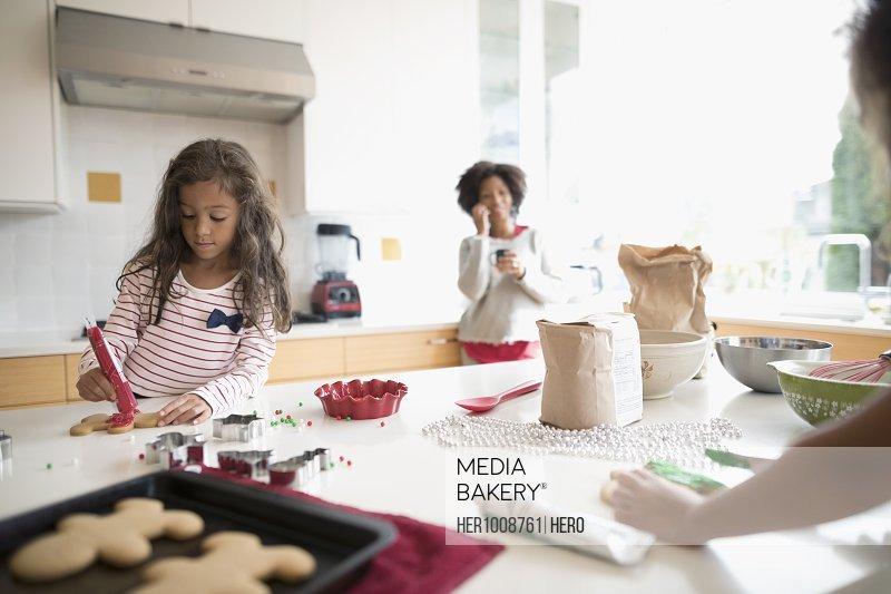 Mother and daughters decorating Christmas gingerbread cookies in kitchen