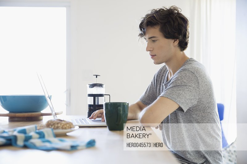 Young man drinking coffee working at laptop in kitchen