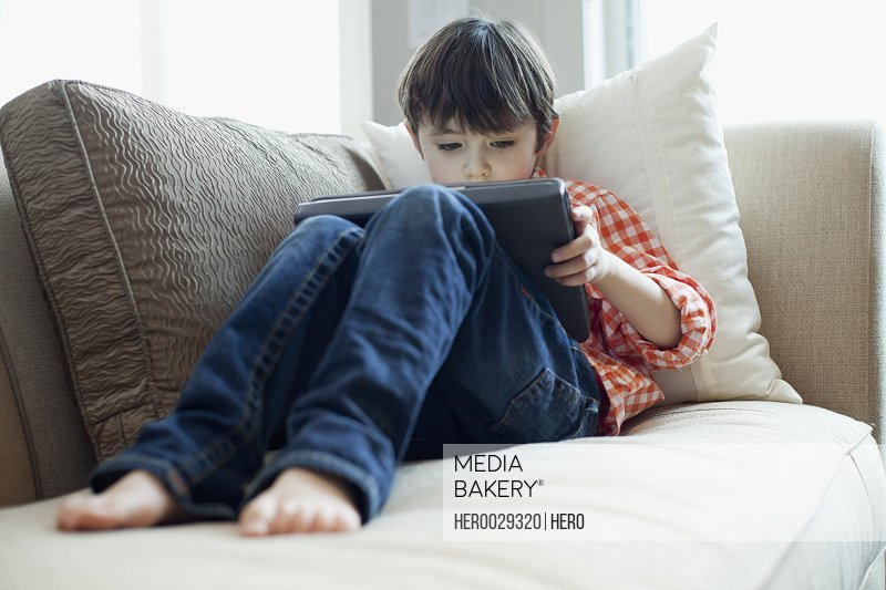 young boy playing on ipad