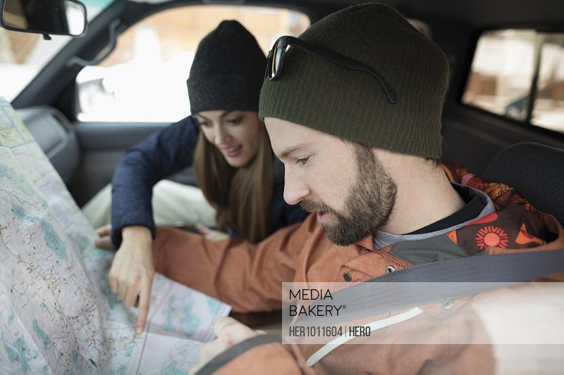 Adventurous couple checking map in truck
