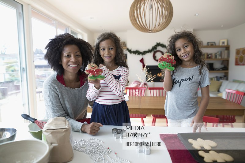 Portrait smiling mother and daughters decorating Christmas gingerbread cookies in kitchen