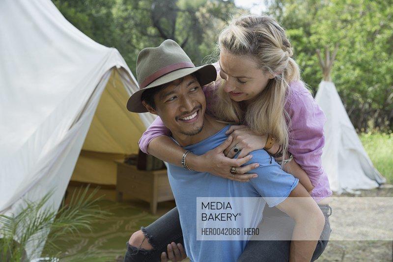 Young couple piggybacking outside camping yurt
