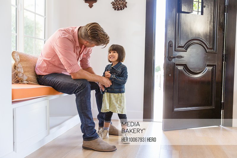 Toddler daughter smiling at father in foyer entry