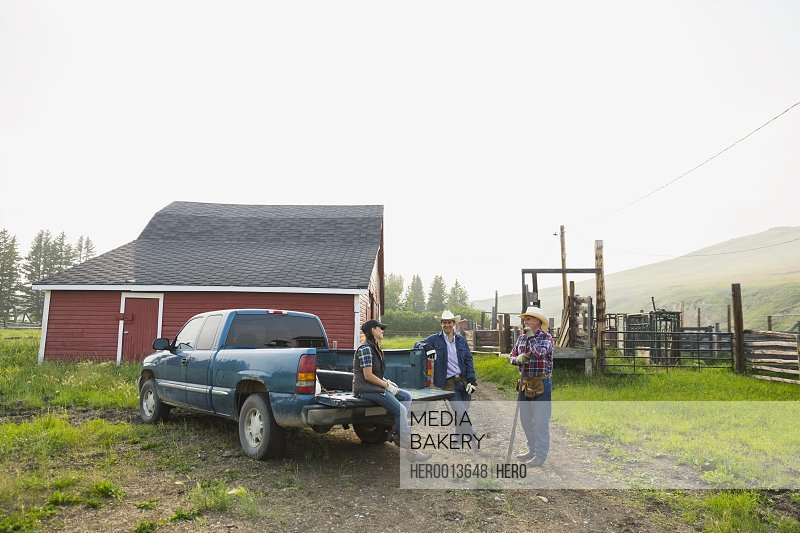 Ranchers talking at truck outside barn