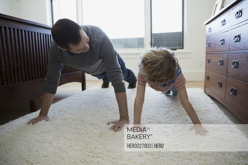 Father teaching son push-ups on bedroom rug