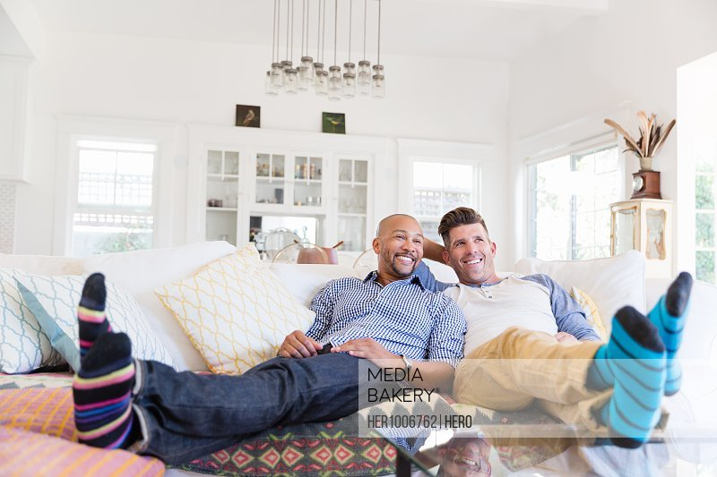 Comfortable male gay couple in striped socks relaxing, watching TV on living room sofa