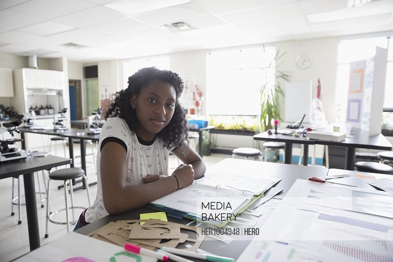 Portrait confident girl middle school student working on science project in classroom