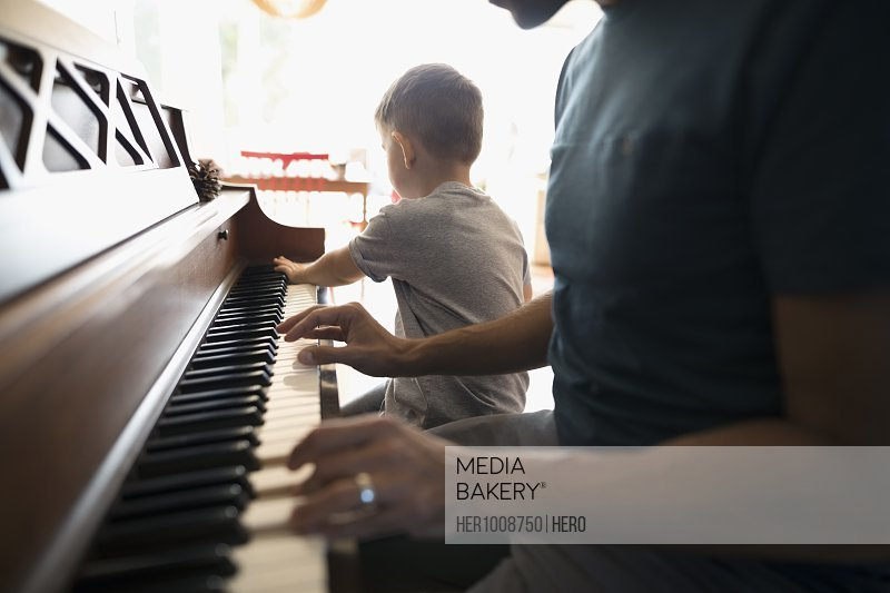 Father teaching toddler son playing piano
