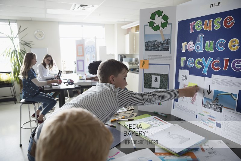 Boy middle school student working on recycling science project in classroom