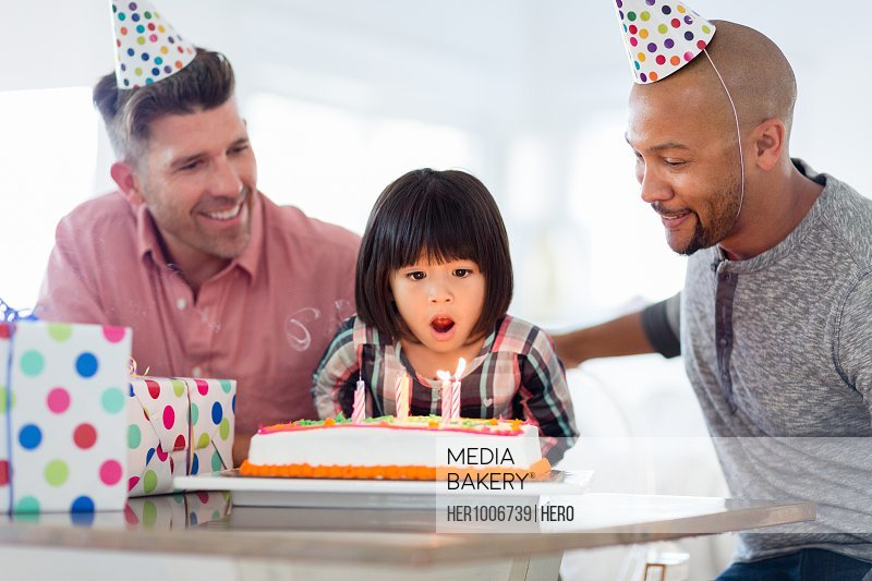 Male gay parents watching adopted toddler daughter make a wish, blow out birthday candles on cake