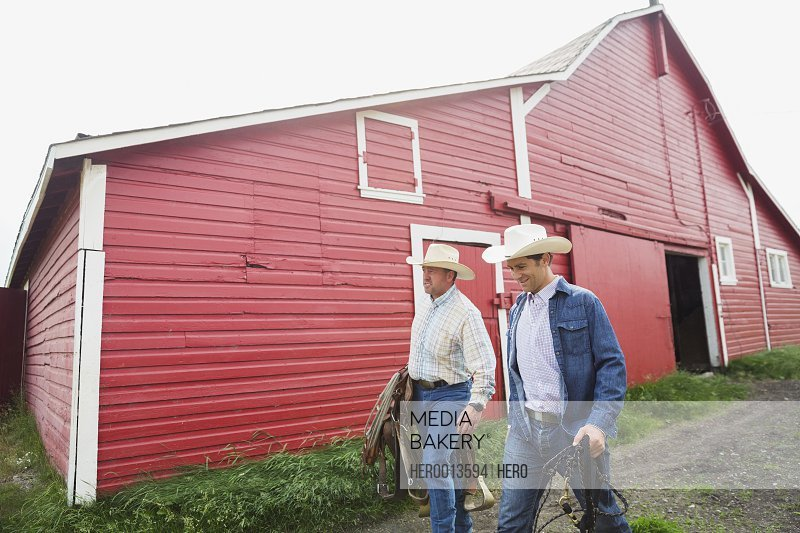 Ranchers carrying saddle and tack outside barn