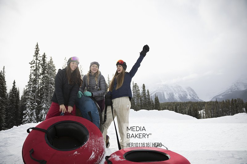 Exuberant female friends with inner tubes in snow