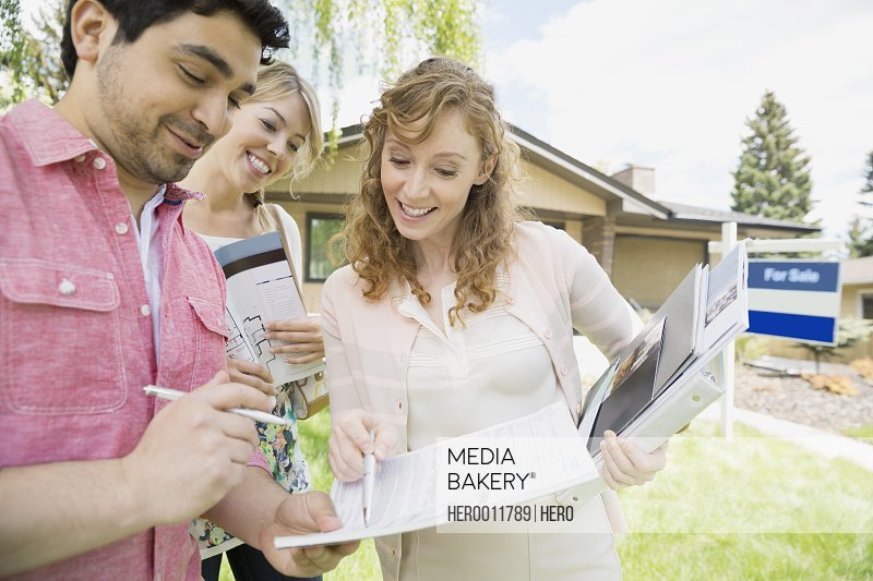Couple signing paperwork with realtor outside house