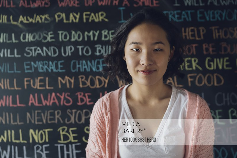 Portrait smiling, confident Korean tween girl against wall with chalk text
