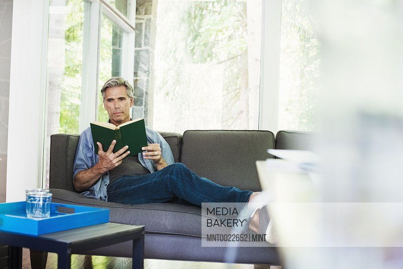 A man sitting by a window on a sofa reading a book