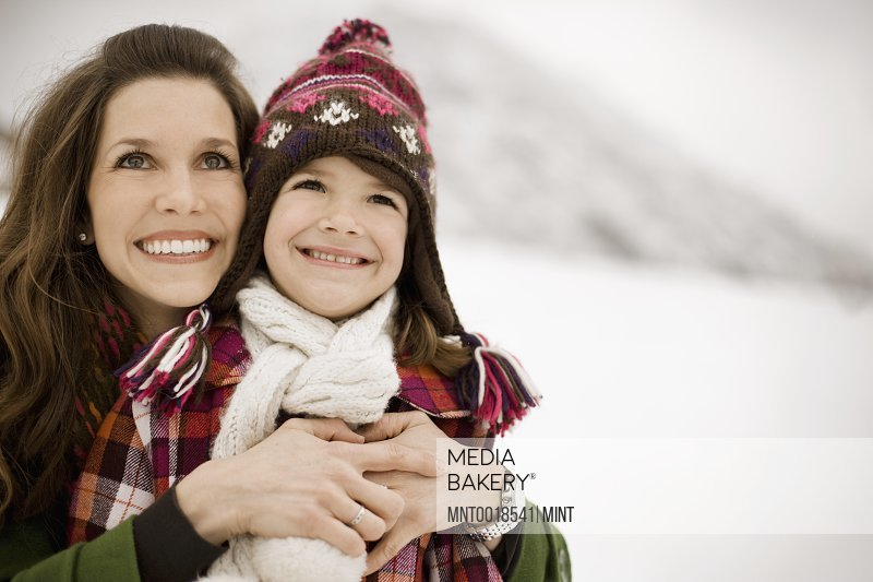 A woman and a child hugging smiling broadly in the snowy mountains