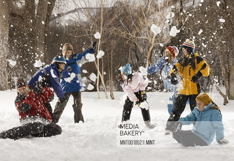 Four people outdoors in hats coats and scarves having an energetic snowball fight