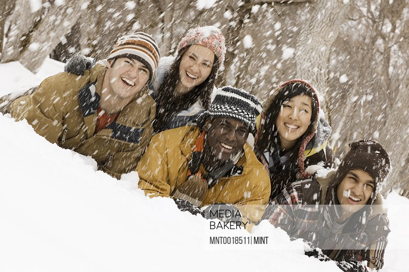Five young people lying on the snow laughing Snow falling