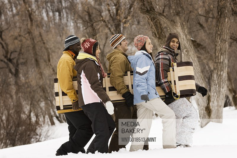 Five young people carrying a wooden sledge across the snow