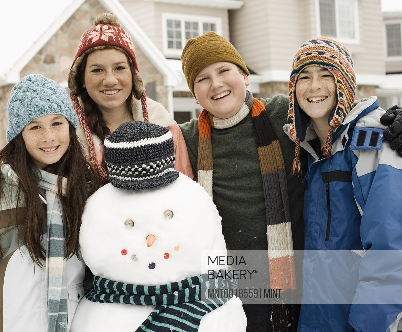 Winter snow Four children two boys and two girls by a snowman figure wearing a scarf and hat