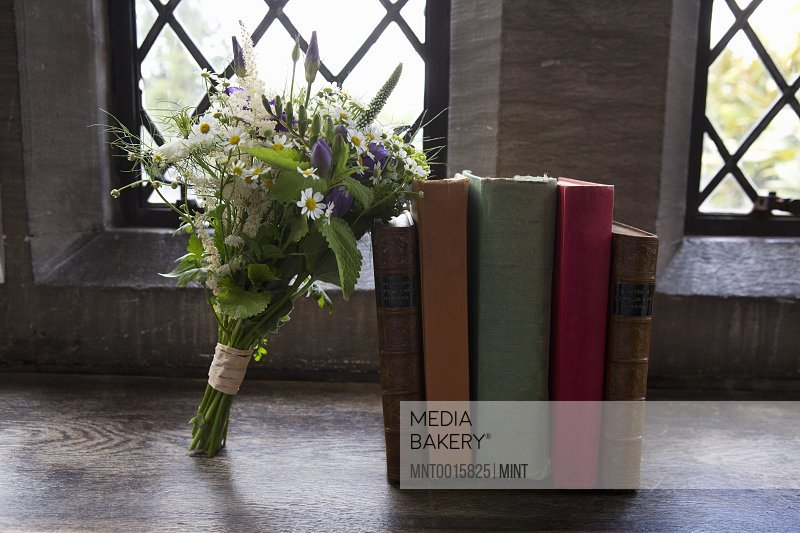 A bouquet of blue and white wedding flowers leaning against books.