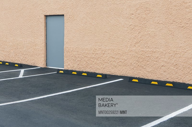 A car park with lined bays outside a building and a door in a wall.