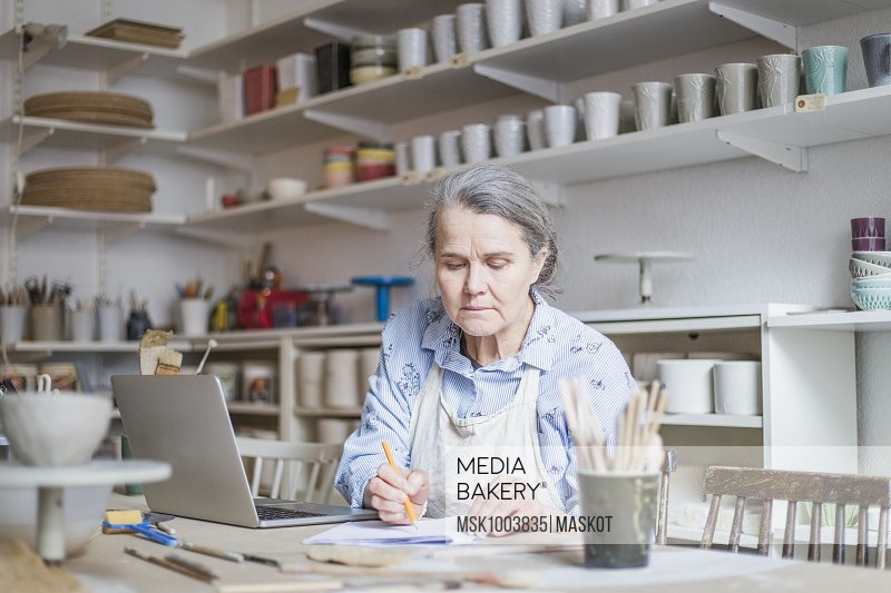 Senior female potter writing on paper while sitting with laptop at table in workshop