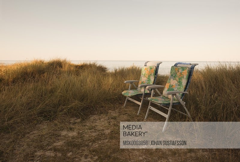 Two chairs at beach against clear sky