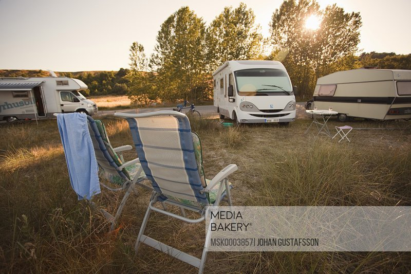 Campervans and chairs on field