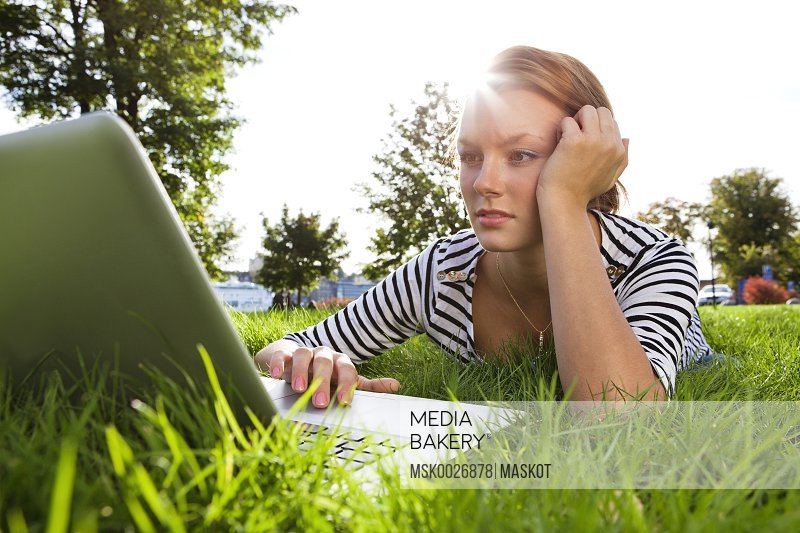 Woman lying on grass while using laptop