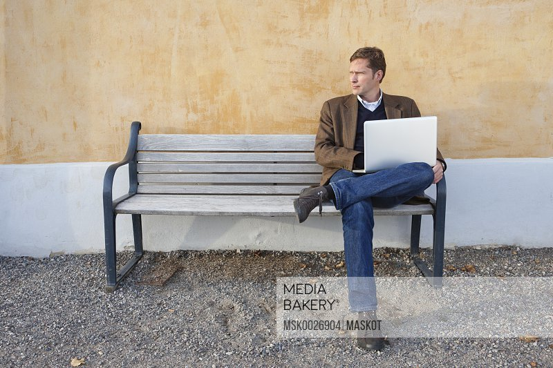 Man sitting on bench with laptop on his lap