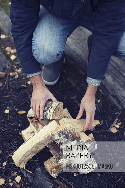 Low section of man arranging wood for bonfire