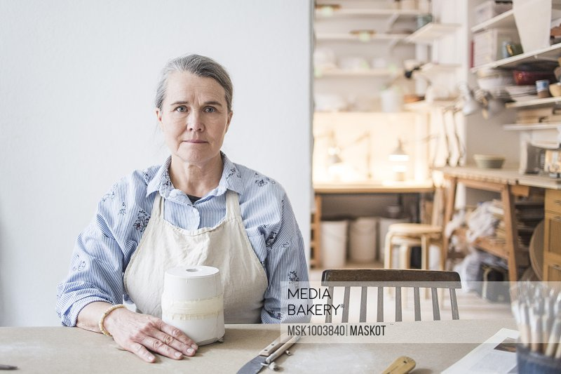Portrait of confident senior female potter sitting at table with vase against white wall in workshop