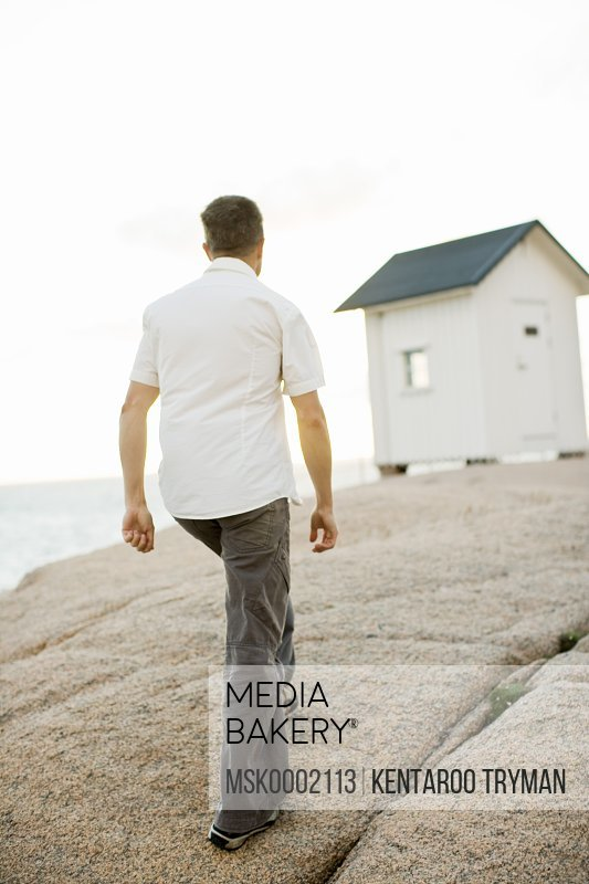Rear view of man walking on rock with cabin in background
