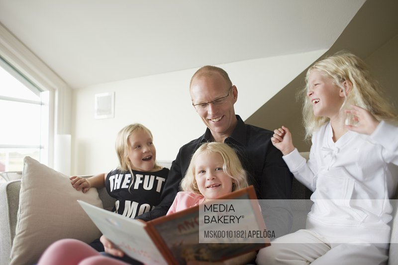 Father reading for three daughters