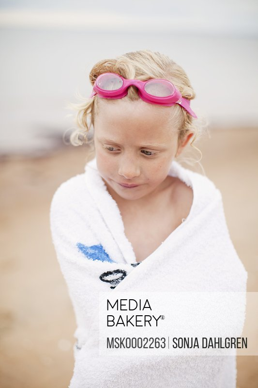Young blond girl wrapped in a towel wearing swimming goggles