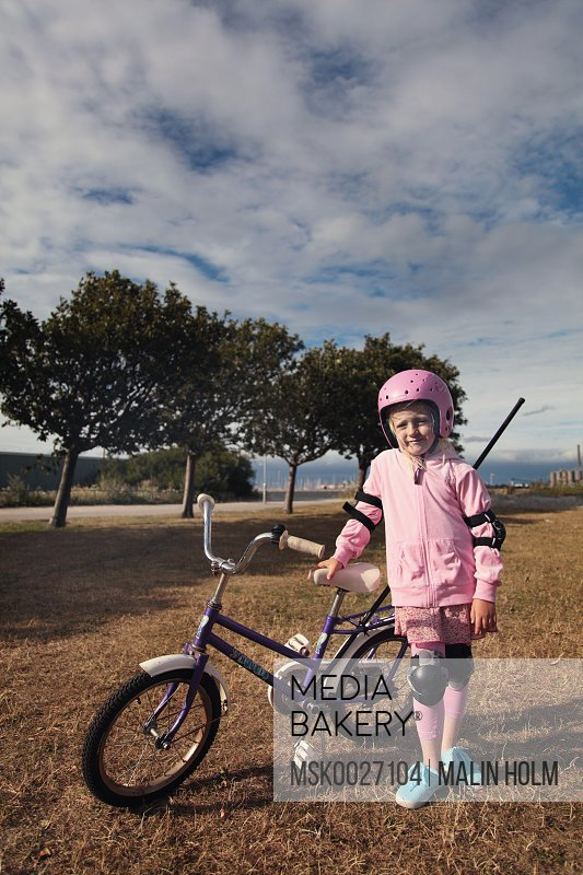 Girl 6-7 leaning on bicycle