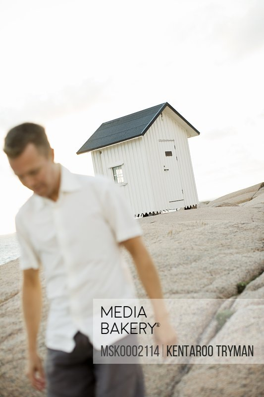 Man walking on rock with log cabin in background
