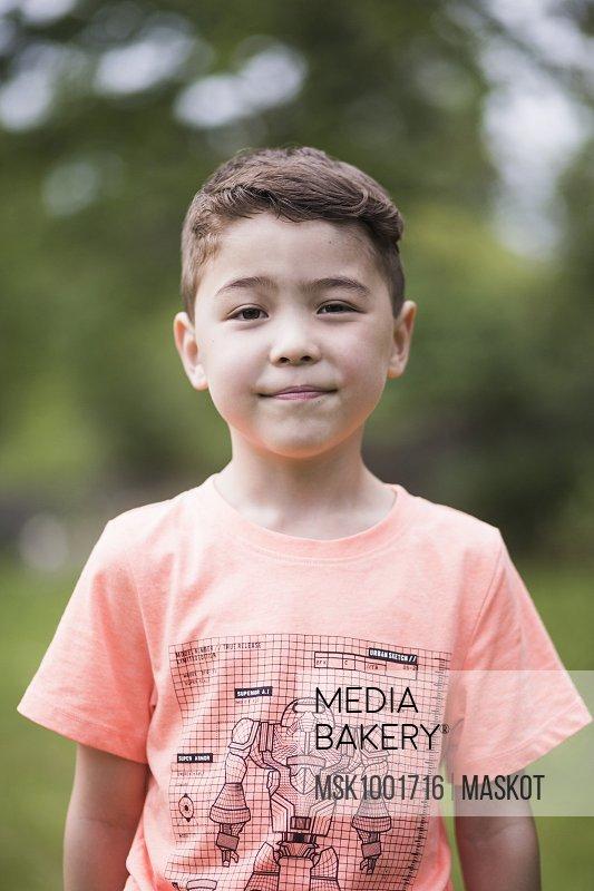 Portrait of boy standing in back yard
