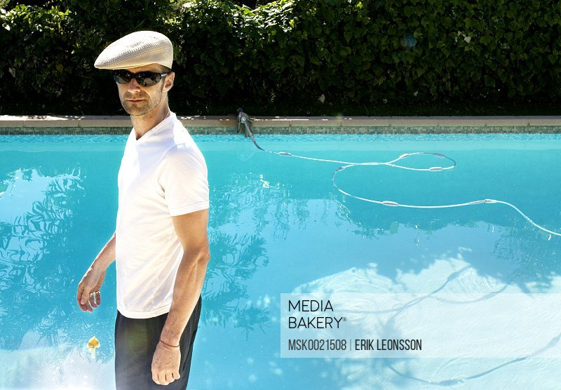 Young man in a cap by the pool