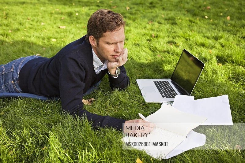 Man writing on book while lying on grass