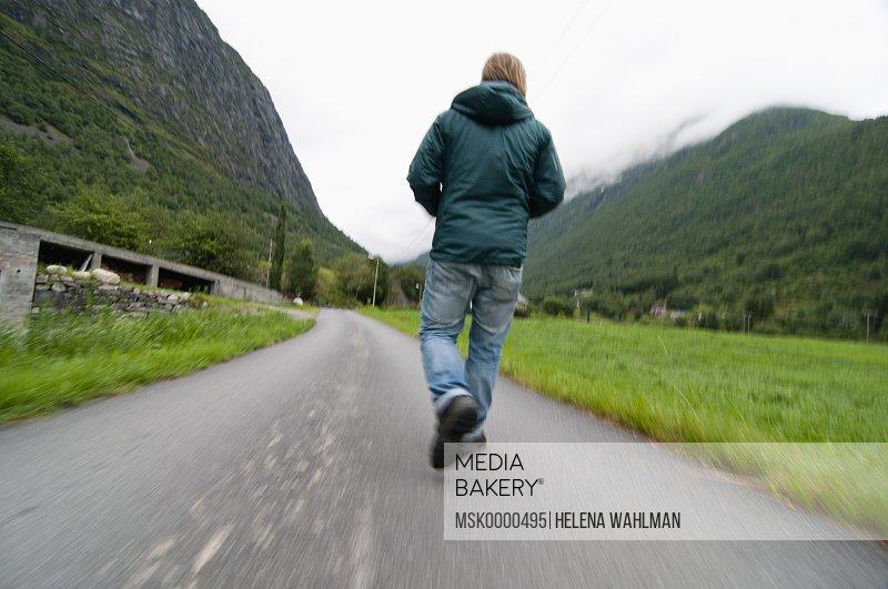 Rear view of man walking on road