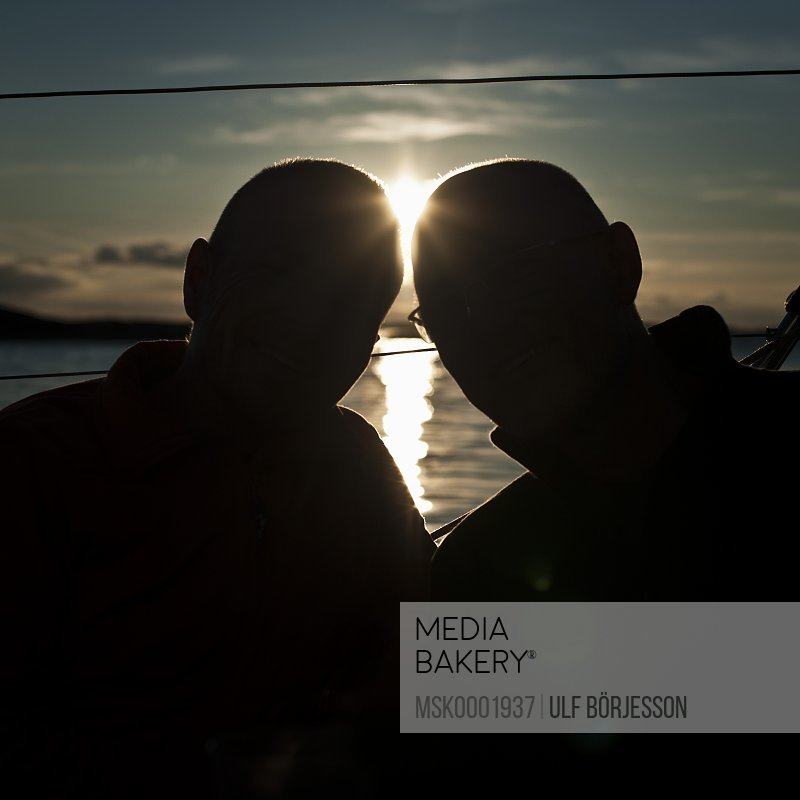 Silhouette image of two males with sun in background
