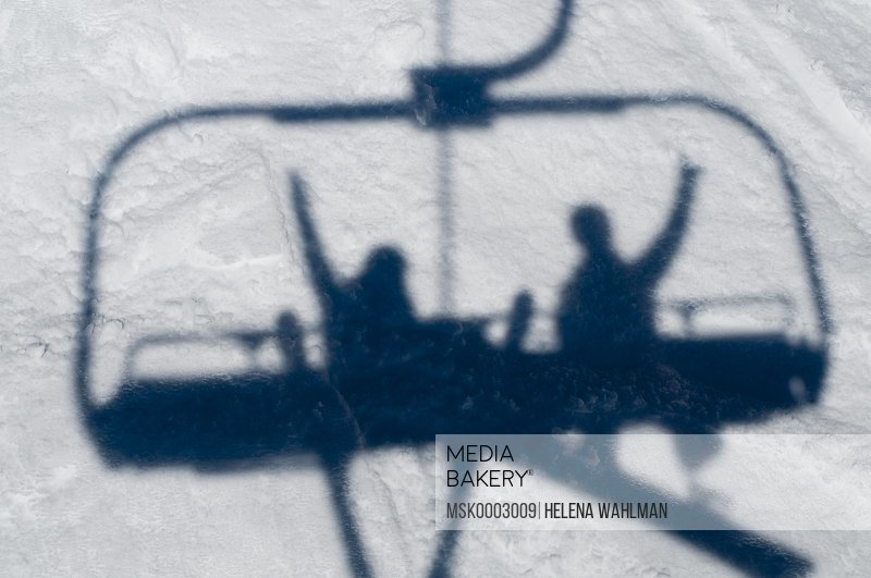 Shadows of skiers on a chairlift