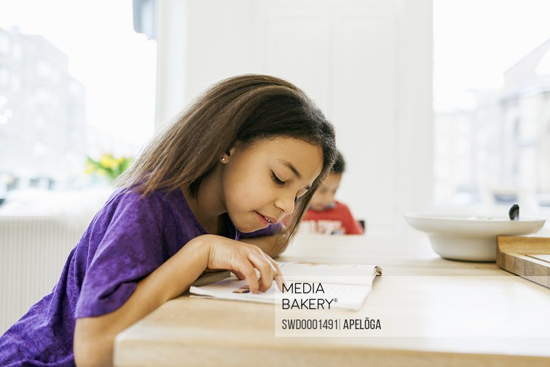 Side view of girl reading book with brother in background at kitchen