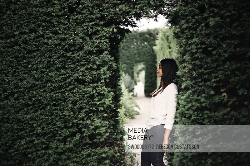 Young woman leaning on bushes in park