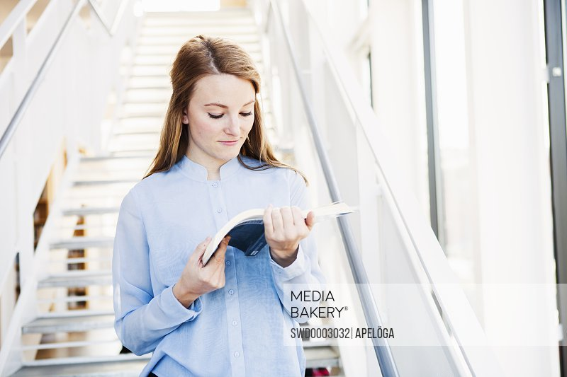 Young woman reading book while standing against steps in library